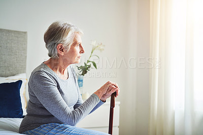 Buy stock photo Shot of a senior woman looking thoughtful while holding a walking stick at home