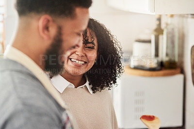 Buy stock photo Shot of a young couple cooking together in their kitchen at home