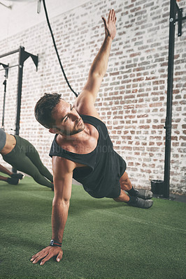 Buy stock photo Shot of a man doing the side plank at the gym