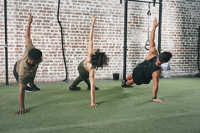 Buy stock photo Shot of a fitness group doing the side plank together at the gym