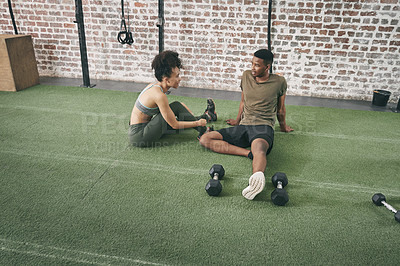 Buy stock photo Shot of two sporty young people having a conversation while sitting together at the gym