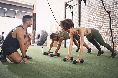 Buy stock photo Shot of two people working out with a fitness instructor at the gym