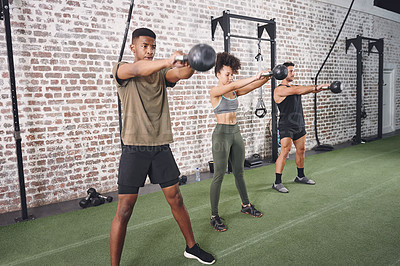Buy stock photo Shot of a fitness group working out using kettlebells at the gym