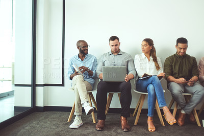 Buy stock photo Shot of a diverse group of businesspeople sitting in a line in the office