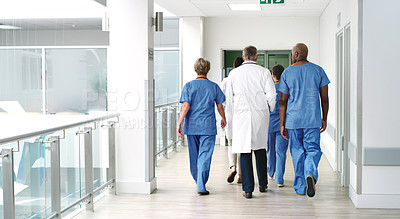 Buy stock photo Shot of a diverse group of uunrecognizable medical practitioners walking in the hallway of the hospital