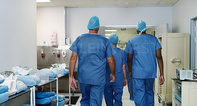 Buy stock photo Shot of an unrecognizable group of medical practitioners walking through the doors of the ward into the hallway of the hospital