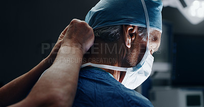 Buy stock photo Shot of an unrecognizable surgical nurse fastening the medical mask of a male doctor in the operating theatre