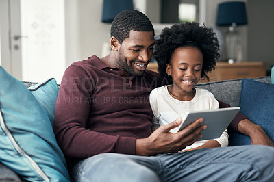 Buy stock photo Shot of a little girl and her father looking at something on a digital tablet while sitting at home