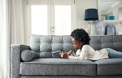 Buy stock photo Shot of an adorable little girl using a digital tablet while lying on the couch at home