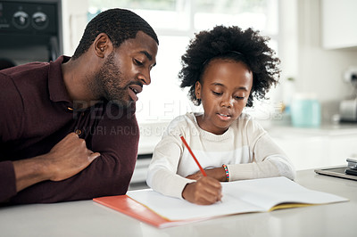 Buy stock photo Shot of a man helping his daughter with her homework at home