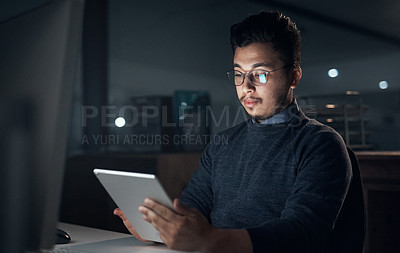 Buy stock photo Shot of a young businessman using a digital tablet and computer during a late night in a modern office