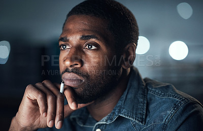 Buy stock photo Shot of a young businessman looking thoughtful during a late night in a modern office
