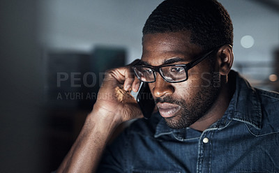 Buy stock photo Shot of a young businessman using a computer and smartphone during a late night in a modern office
