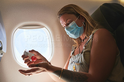 Buy stock photo Shot of a woman sanitising her hands in the aeroplane