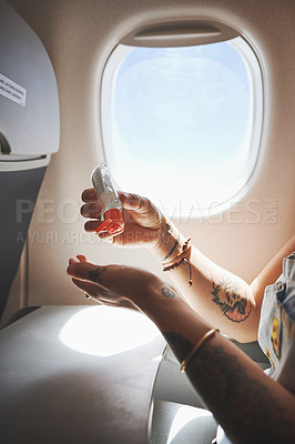 Buy stock photo Cropped shot of a woman sanitising her hands in the aeroplane