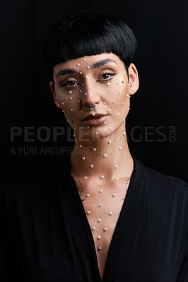 Buy stock photo Studio portrait of a beautiful young woman with pearls on her face posing against a black background