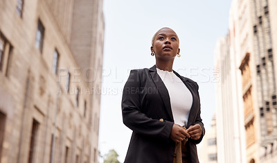 Buy stock photo Low angle shot of a young businesswoman looking thoughtful while standing in the city