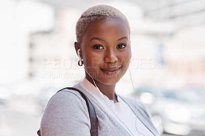 Buy stock photo Portrait of a young businesswoman wearing earphones while out in the city