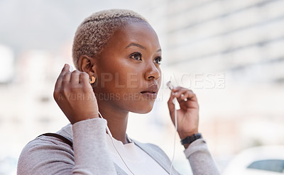 Buy stock photo Shot of a young businesswoman wearing earphones while out in the city