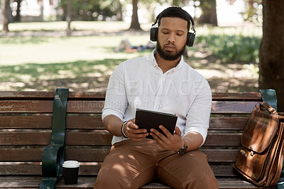 Buy stock photo Shot of a young businessman wearing headphones and using a digital tablet while sitting on a bench outdoors