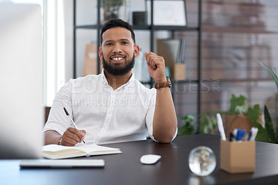 Buy stock photo Portrait of a young businessman writing notes in an office