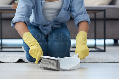 Buy stock photo Shot of an anonymous woman using a dustpan and sweeping her living room floor at home