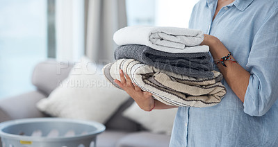 Buy stock photo Shot of an anonymous woman holding a pile of clean neatly folded laundry