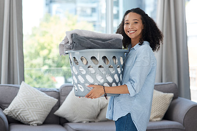 Buy stock photo Shot of a young woman holding a laundry basket of folded clothing at home