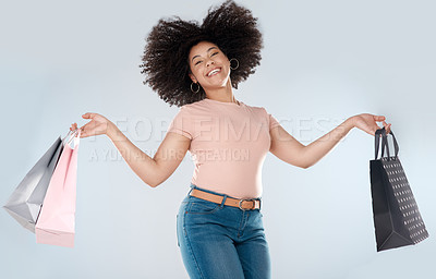 Buy stock photo Studio portrait of a young woman jumping while carrying a bunch of shopping bag