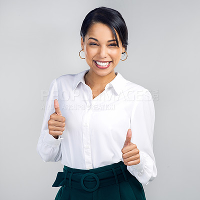 Buy stock photo Studio shot of a confident young businesswoman giving a thumbs up against a grey background