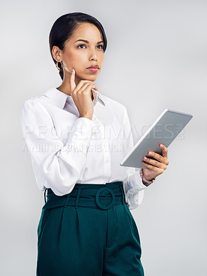 Buy stock photo Studio shot of a young businesswoman using a digital tablet and looking thoughtful against a grey background
