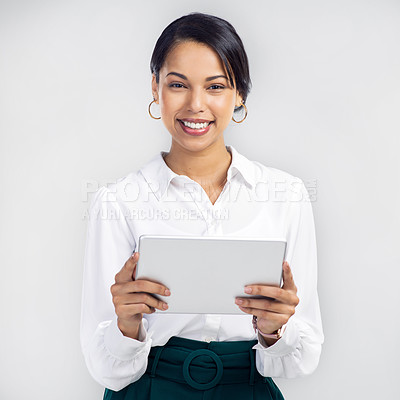 Buy stock photo Studio shot of a young businesswoman using a digital tablet against a grey background