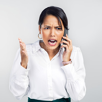 Buy stock photo Studio shot of a young businesswoman using a smartphone and yelling against a grey background