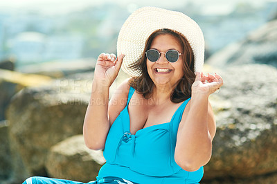 Buy stock photo Shot of an attractive mature woman sitting alone during a day out on the beach