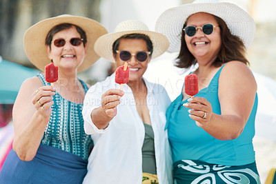 Buy stock photo Shot of a mature group of friends standing together and enjoying ice cream while bonding on the beach