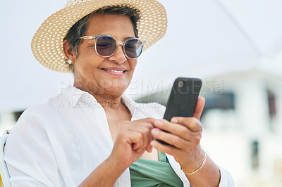 Buy stock photo Shot of a mature woman sitting alone and using her cellphone during a day out on the beach