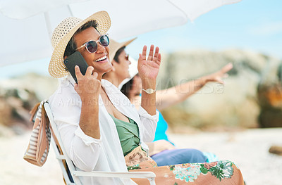 Buy stock photo Shot of a mature woman sitting alone and using her cellphone during a day out on the beach with friends