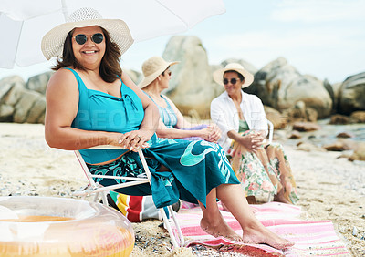 Buy stock photo Shot of a mature woman sitting and enjoy a day out on the beach with friends