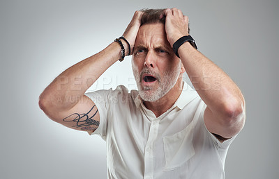Buy stock photo Studio shot of a mature man looking disappointed against a grey background