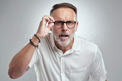 Buy stock photo Studio portrait of a mature man wearing spectacles and looking confused against a grey background