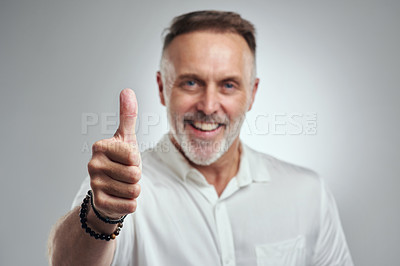 Buy stock photo Studio portrait of a mature man showing thumbs up against a grey background