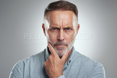 Buy stock photo Studio portrait of a mature man looking thoughtful against a grey background