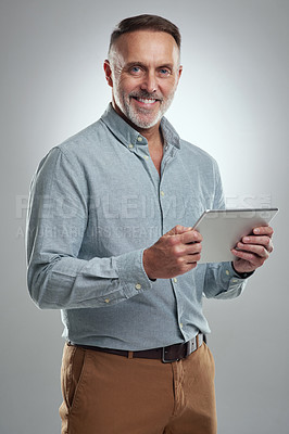 Buy stock photo Studio portrait of a mature man using a digital tablet against a grey background