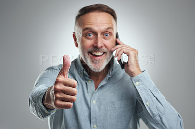 Buy stock photo Studio portrait of a mature man showing thumbs up while talking on a cellphone against a grey background