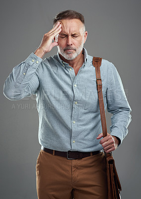 Buy stock photo Studio shot of a mature man experiencing a headache and looking stressed out against a grey background