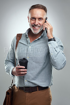Buy stock photo Studio portrait of a mature man talking on a cellphone while carrying a bag and cup of coffee against a grey background