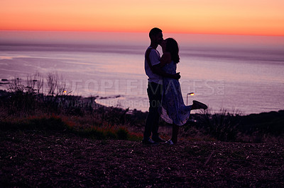 Buy stock photo Full length shot of an affectionate young couple silhouetted at sunset