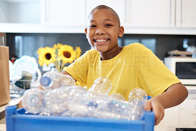 Buy stock photo Shot of a young boy getting ready to recycle some bottles at home