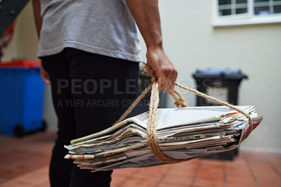 Buy stock photo Cropped shot of a unrecognizable man on his way to recycle newspaper at home