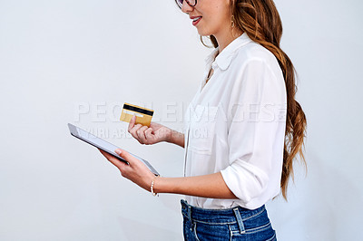 Buy stock photo Cropped shot of an unrecognizable businesswoman standing against a white wall and using a digital tablet for online shopping